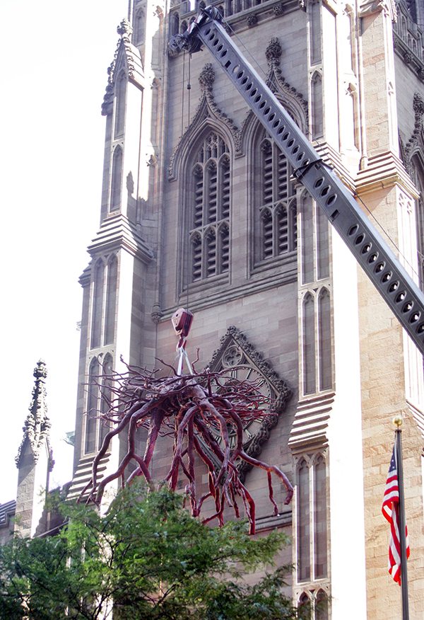 "NEW YORK - SEPTEMBER 8: Guided by workmen, the ""Trinity Root"" sculpture is lowered into place by a crane in the Trinity Church yard September 8, 2005 in New York CIty. The three-ton, 121/2 foot by 20 foot bronze memorializes the stump of the 70-year-old sycamore tree that shielded St. Paul's Chapel from falling debris on September 11, 2001. (Photo by Stephen Chernin/Getty Images)"